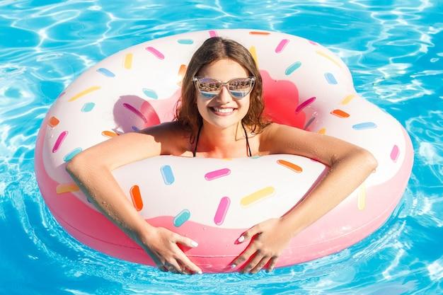 Hermosa chica está nadando en el anillo inflable de donas