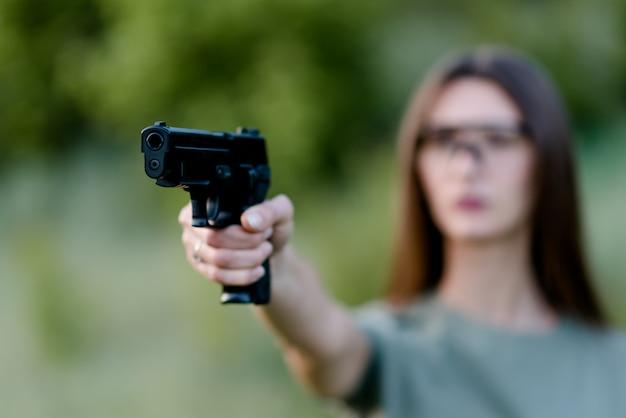 Hermosa chica en la naturaleza aprende a disparar una pistola