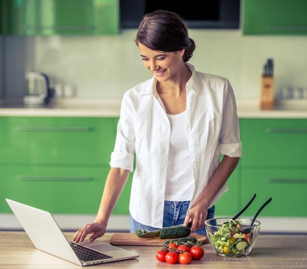Hermosa chica de negocios está utilizando una computadora portátil y sonriendo.