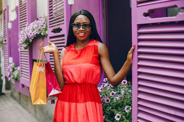 Hermosa chica negra con bolsas de compras en una ciudad
