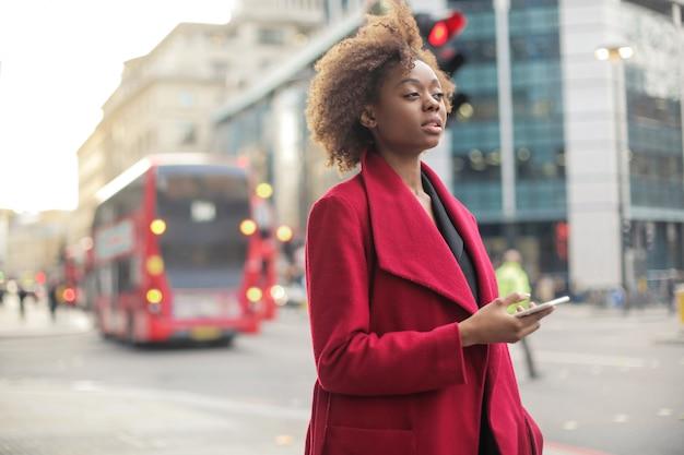 Hermosa chica negra caminando por la calle, revisando su teléfono