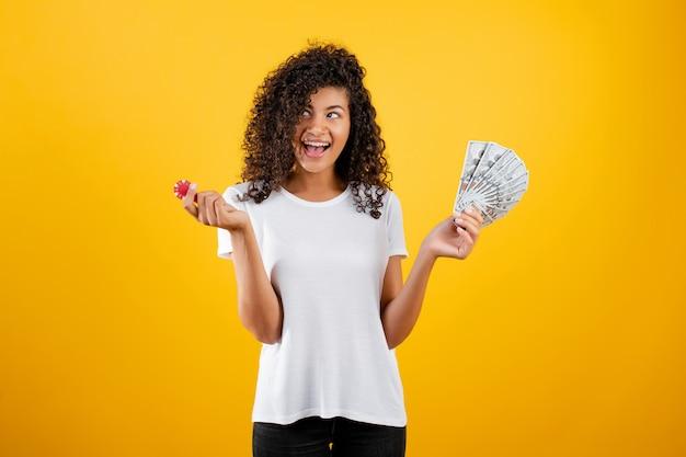 Hermosa chica negra con ficha de póker del casino en línea y dinero en dólares aislado sobre amarillo