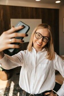 Una hermosa chica en la oficina hace un selfie en el teléfono, una foto en un teléfono inteligente en el trabajo.