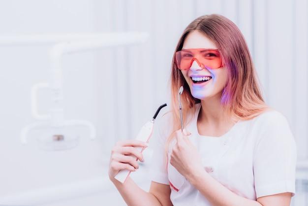Hermosa chica ortodoncista posando con instrumentos en clínica