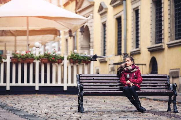 Hermosa chica de otoño sentada en un banco en medio de la acera en el café