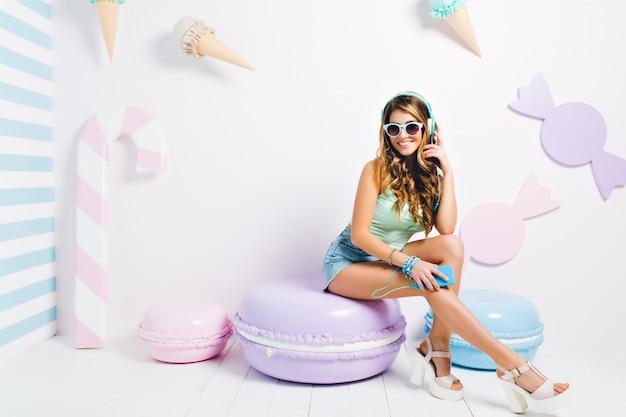 Hermosa chica en pantalones cortos de mezclilla descansando sobre la almohada de galletas jugando con el pelo y sonriendo. retrato de mujer joven alegre escuchando música en el teléfono y posando en la pared decorada con caramelos de color púrpura.