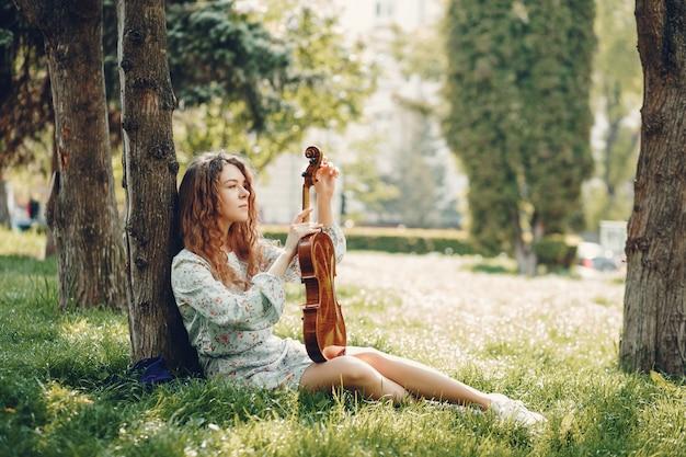 Hermosa chica en un parque de verano con un violín