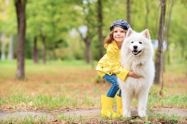 Hermosa chica en un paseo con un hermoso perro en un parque al aire libre