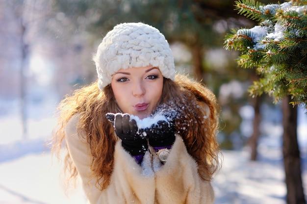 Hermosa chica en un paseo por el parque en invierno