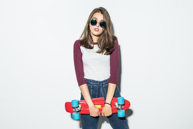 Hermosa chica patinadora en ropa casual y gafas de sol negras con patineta roja aislada en la pared blanca