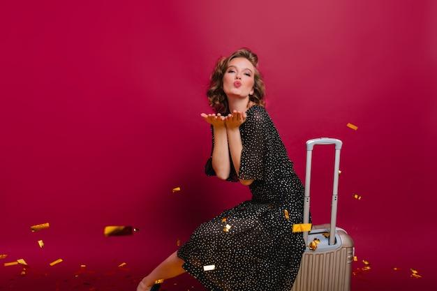 Hermosa chica con peinado corto y elegante envía besos al aire, mientras está sentada en la maleta