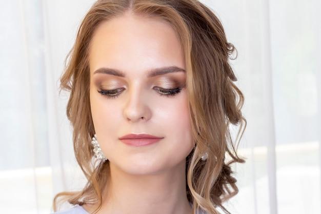 Hermosa chica con un peinado de novia se mira en el espejo, retrato de una joven. hermoso maquillaje. salón de belleza