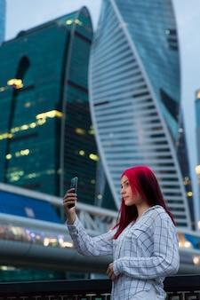 Hermosa chica pelirroja haciendo selfie en smartphone por la noche en la calle iluminada de la ciudad.
