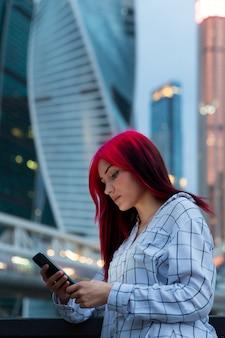 Hermosa chica pelirroja con smartphone en la noche en la calle iluminada de la ciudad.