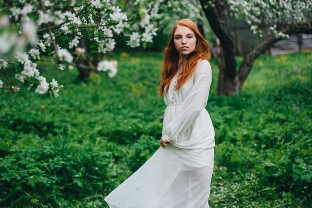 Hermosa chica pelirroja con un vestido blanco entre florecientes manzanos en el jardín.