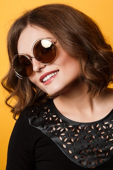 Hermosa chica con el pelo corto, sonriente y con gafas de sol. maquillaje de noche, lápiz labial desnudo, sonrisa blanca