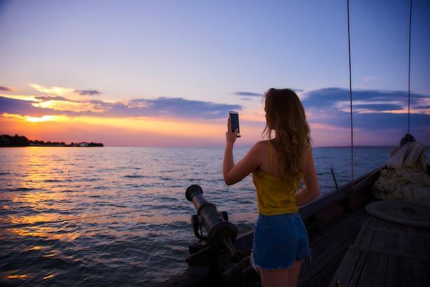 Hermosa chica con el pelo largo se encuentra con el amanecer. velero en el mar al atardecer
