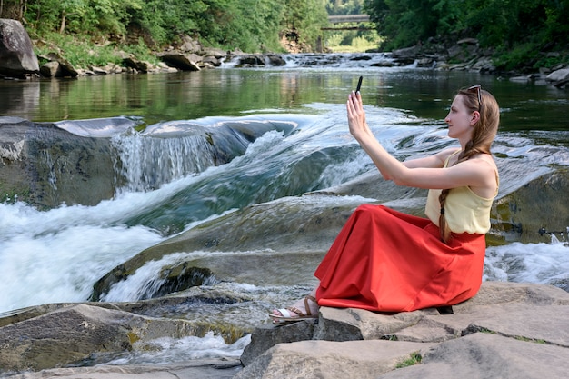 Hermosa chica de pelo largo en una falda roja sentada en una roca y haciendo selfie en el espacio de una cascada del río de montaña. tarde de verano