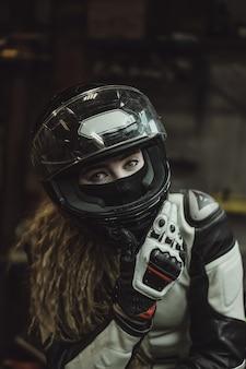 Hermosa chica con el pelo largo en el garaje reparando una motocicleta.
