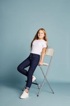 Hermosa chica con el pelo largo sentado en la silla