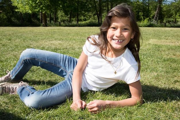 Hermosa chica con el pelo largo tumbado en la hierba verde