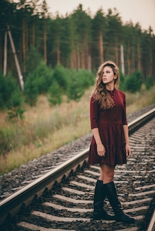 Hermosa chica con el pelo rizado natural disfruta de la naturaleza en el bosque en ferrocarril. soñadora dama en vestido burdeos a pie en ferrocarril.