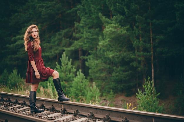 Hermosa chica pensativa triste con el pelo rizado natural en la naturaleza en el bosque en ferrocarril. soñadora dama en vestido burdeos a pie en ferrocarril. chica deprimida sobre rieles al amanecer. sol en el pelo en otoño. mal humor.