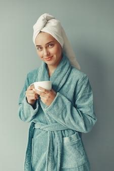 Hermosa chica de pie en una bata de baño azul