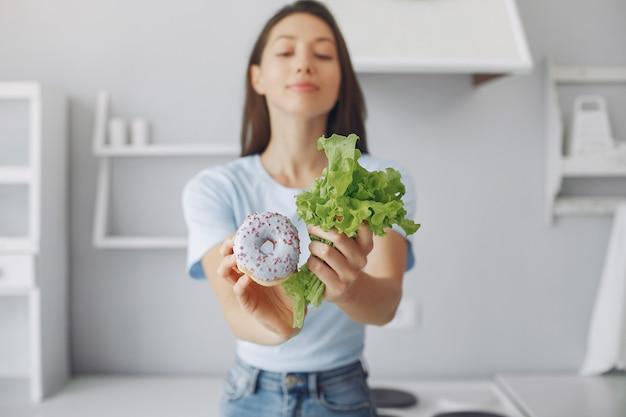 Hermosa chica de pie en una cocina con donas y hojas