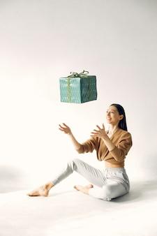 Hermosa chica de pie en un estudio con regalos