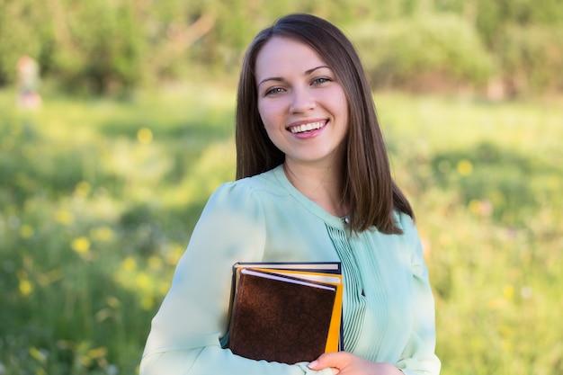 Hermosa chica de pie con libros en sus manos