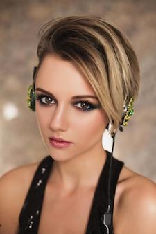 Hermosa chica con piel bronceada y cabello blanco escuchando música con auriculares. retrato de belleza femenina de un hermoso maquillaje. disfrutando de buena musica