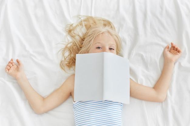 Hermosa chica con pijama, leyendo cuentos de hadas en la cama, cubriéndose la cara con un libro.