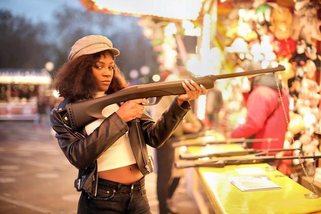 Hermosa chica con una pistola falsa en un luna park
