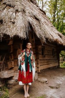 Hermosa chica posa en los patios cerca de la casa con un vestido tradicional ucraniano
