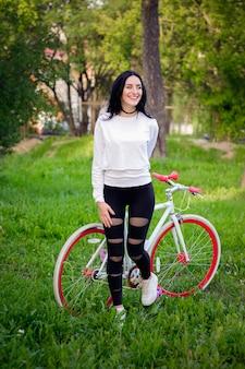 Hermosa chica posando en una bicicleta. bicicleta blanca y roja. caminar en la naturaleza estilo de vida saludable. fin de semana en la naturaleza retrato de una hermosa niña feliz en una camiseta blanca. lugar para escribir