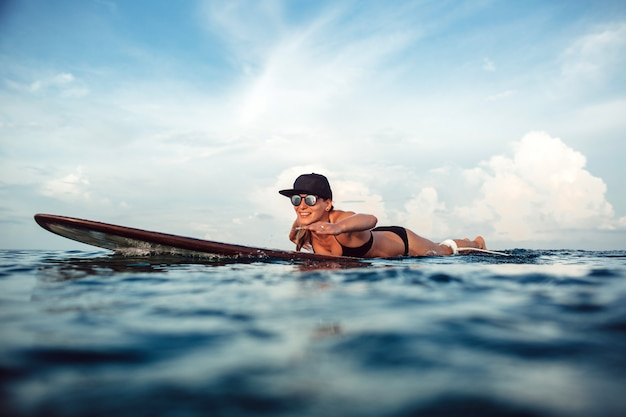Hermosa chica posando sentado en una tabla de surf en el océano