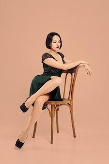 Hermosa chica posando en silla en estudio