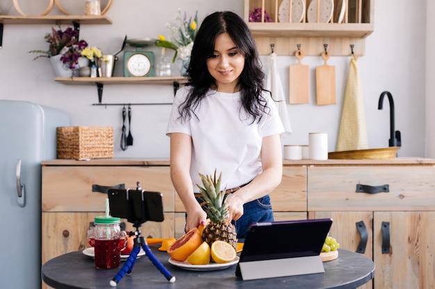Hermosa chica prepara deliciosa comida saludable y graba video para su blog