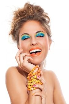 Hermosa chica con pulsera artesanal y maquillaje artístico.