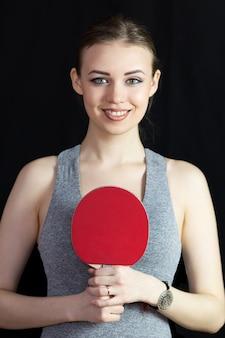 Hermosa chica con una raqueta para tenis de mesa sobre un fondo negro.