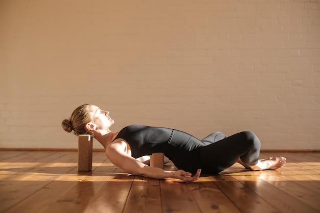 Hermosa chica relajante practicando yoga restaurativo