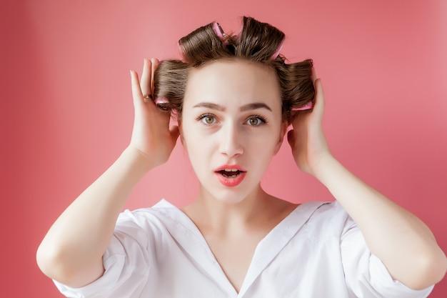 Hermosa chica en rizadores para el cabello sobre fondo rosa