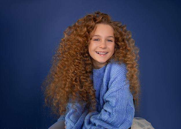 Hermosa chica con rizos afro de pelo rojo sonríe ampliamente sobre fondo azul. pecas en la cara. coloración del cabello, cuidado de la piel para adolescentes.