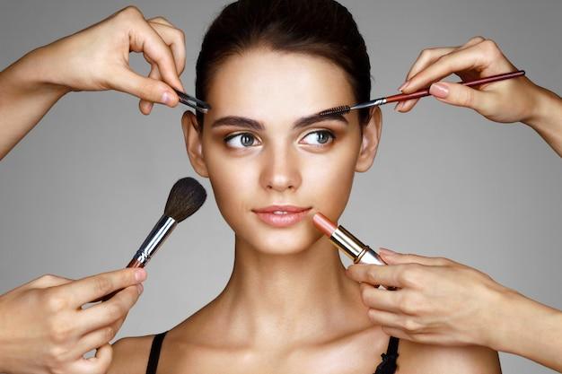 Hermosa chica rodeada de manos de maquilladores con pinceles y lápiz labial cerca de su cara