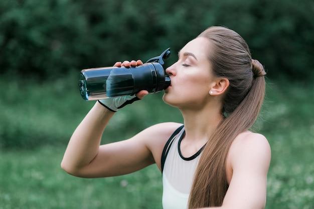 Hermosa chica en ropa deportiva, agua potable después del entrenamiento mientras está sentada en la hierba