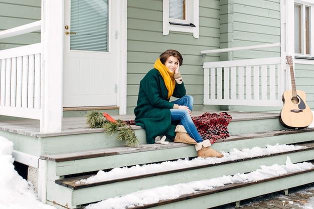 Hermosa chica en ropa elegante en un caryl en casa
