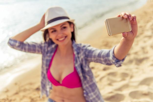 Hermosa chica en ropa de verano está haciendo selfie.