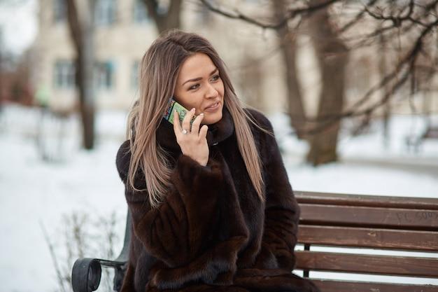 Hermosa chica rubia apariencia caucásica en un abrigo de piel sentado en un parque en un banco en el invierno y hablando por teléfono