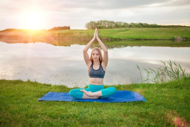 Hermosa chica rubia atlética practicando yoga en el lago al atardecer, primer plano, apoya un estilo de vida saludable